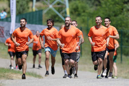 grime: Sofia, Bulgaria - July 9, 2016: Participants are running in a group at the Legion Run extreme sport challenge near Sofia. The sports event is mud and obstacle course designed to test peoples physical strength, stamina, and mental grit.