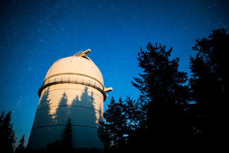 hundreds: Rozhen astronomical observatory under the night sky stars. Blue sky with hundreds of stars of the Milky way. Observatory in a pine trees forest in the mountain. Moon light. Vignetting.