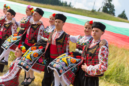 Rozhen, Bulgarie - 15 Juillet, 2016: danseurs bulgares en costumes folkloriques areposign pour une photo devant le drapeau bulgare avant d'aller sur scène pour leur spectacle de danse.
