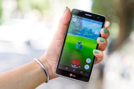 Sofia, Bulgarie - le 23 Juillet, 2016: Femme tient dans sa main un téléphone mobile montrant à l'écran Pokemon Go réalité augmentée jeu mobile. Jouer dans le parc. Zubat. Éditoriale