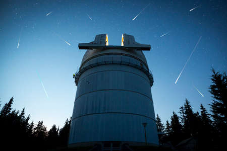 hundreds: Rozhen astronomical observatory under the night sky stars. Blue sky with hundreds of stars of the Milky way. Bulgarian National Astronomical Observatory (Rozhen Observatory). Meteor shower. Falling stars.