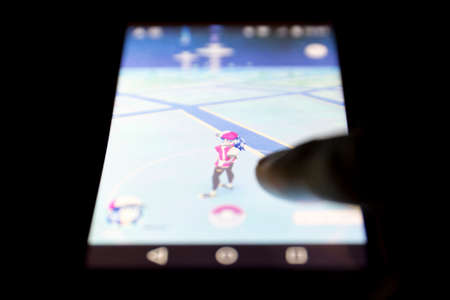 gmail: Sofia, Bulgaria - July 22, 2016: A mobile phone showing on screen Pokemon Go augmented reality mobile game isolated on a black background. Human hand touching the screen. Editorial