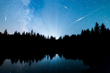 A view of the stars of the Milky Way with a silhouette of a pine trees forest near a lake in the mountain. Falling stars reflection in the water. Comets. Perseid Meteor Shower in 2016. Stock Photo