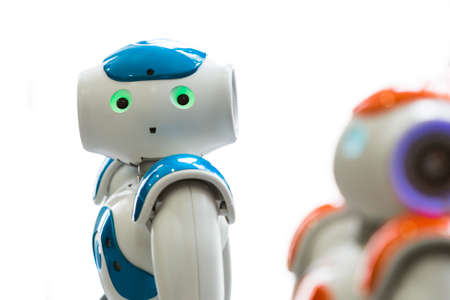 Small robots with human face and body - humanoid. Artificial Intelligence - AI. Orange and blue robots isolated on white background.