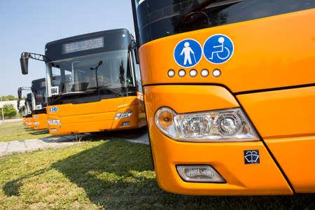 Les nouveaux bus modernes pour les transports en commun sont présentés dans une rangée dans un parking. Physiquement les handicapés et les personnes âgées signes.