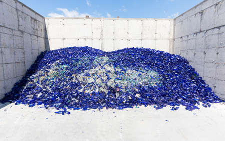 reprocessing: Glass waste for recycling in a recycling facility. Different glass packaging bottle waste. Glass waste management. Glass recycling is the process of waste glass into usable products. Blue bottles.