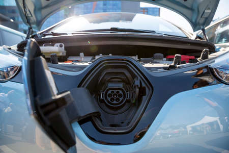 electric automobile: Electric car charger. Electric vehicle charging station. Charger pluged in. An electric car is an automobile that is propelled by one or more electric motors, using electrical energy stored in rechargeable batteries. Stock Photo