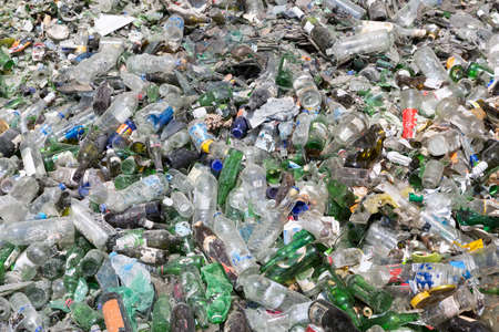 waste products: Glass waste for recycling in a recycling facility. Different glass packaging bottle waste. Glass waste management. Process of waste glass into usable products. Pile of different bottles.