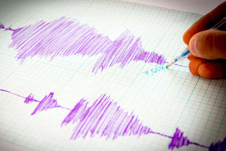 seismology: Seismological device for measuring earthquakes. Seismological activity lines on the sheet of measuring paper. Earthquake wave on graph paper. Vignette image. Human hand writing down with a blue pen.