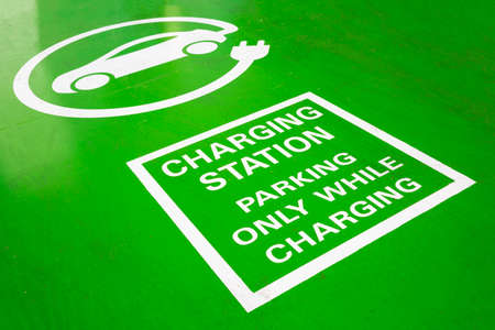 Electric Vehicle Charging Station green road sign. Parking only while charging. An electric car is an automobile that is propelled by one or more electric motors, using electrical energy stored in rechargeable batteries.