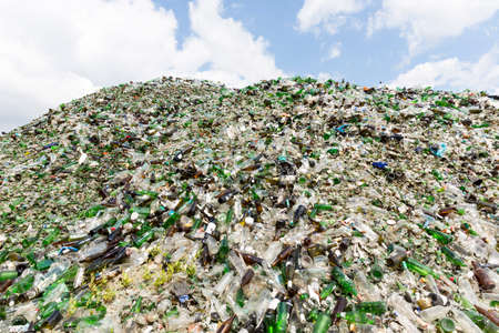 waste management: Glass waste for recycling in a recycling facility. Different glass packaging bottle waste. Glass waste management. Process of waste glass into usable products. Pile of different bottles.