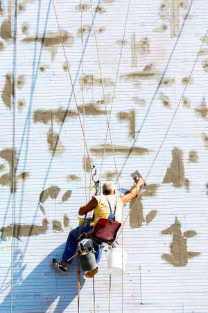 risky job: A worker putting on a buildings thermal and noise isolation is working hanging on ropes on the wall of the building.
