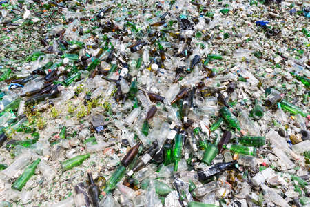reprocessing: Glass waste for recycling in a recycling facility. Different glass packaging bottle waste. Glass waste management. Process of waste glass into usable products. Pile of different bottles.