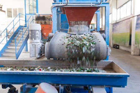 Glass particles for recycling in a machine in a recycling facility. Different glass packaging bottle waste. Glass waste management. Glass recycling is the process of waste glass into usable products.