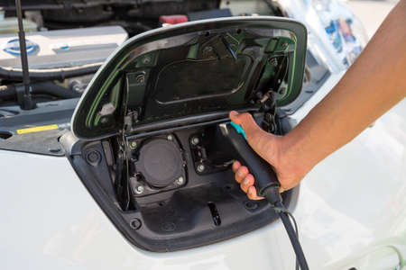 electric vehicle: Electric car charging. Electric vehicle charging station. Human hand pluging in the charger. An electric car is an automobile that is propelled by one or more electric motors, using electrical energy stored in rechargeable batteries. Stock Photo