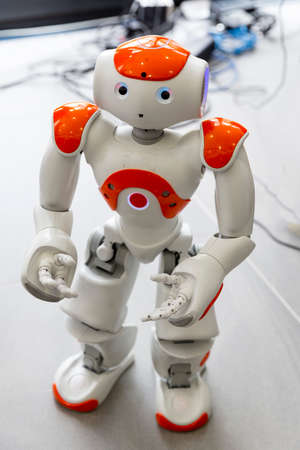 A small robot with human face and body - humanoid. Artificial Intelligence - AI. Orange robot.