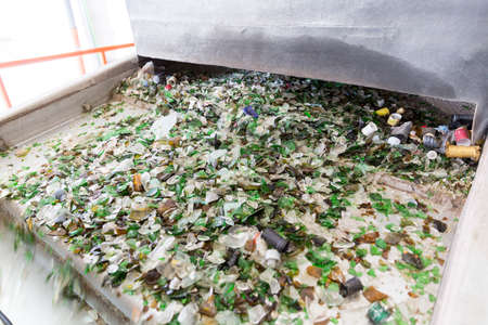 glass recycling: Glass particles for recycling in a machine in a recycling facility. Different glass packaging bottle waste. Glass waste management. Glass recycling is the process of waste glass into usable products.