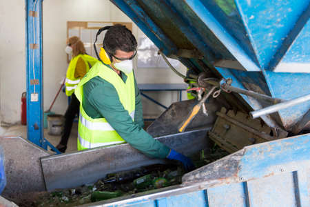 waste management: Sofia, Bulgaria - May 26, 2016: Glass waste worker is recycling glass bottles in a recycling facility. Different glass packaging bottle waste. Glass waste management. Editorial