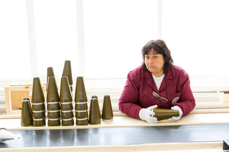 arsenal: Sopot, Bulgaria - May 17, 2016: Arsenal worker is producing warheads in one of Bulgarias arms factory. The facility produces and assembles rocket-propelled grenades (RPG), RPG-7 launchers, RPG war heads, detonators, land mines and others.