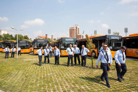 busses: Sofia, Bulgaria - August 31, 2016: New modern busses for public transportation are shown in a row in a parking lot. Bus drivers are standing before them. Editorial