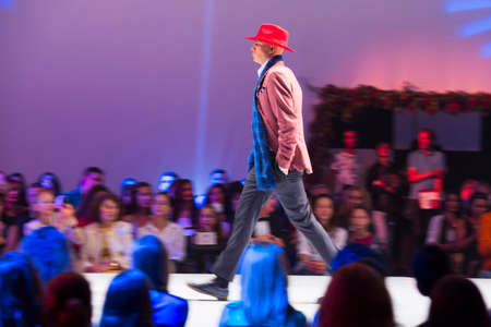 slow motion: Sofia, Bulgaria - September 14, 2016: A male model walks the runway during the AutumnWinter Sofia Fashion Week Show 2016 in Sofia, Bulgaria. Red hat. Slow motion. Editorial