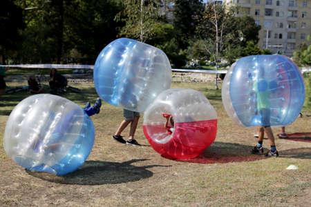 Jongens spelen bubble voetbalwedstrijd in het park.