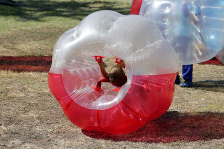 Boys are playing bubble football game in the park.