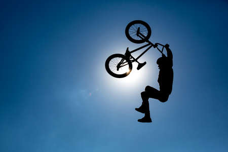 abilities: An extreme rider is making a free style jump from a ramp. The young boy with his bicycle is seen as a silhouette in front of the sun. Stock Photo