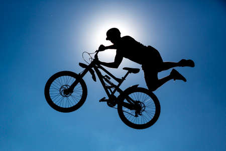 An extreme rider is making a free style jump from a ramp. The young boy with his bicycle is seen as a silhouette in front of the sun. Stock Photo