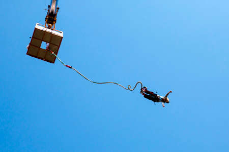 Sofia, Bulgaria - September 25, 2016: An old woman is jumping with a bungee from a crane up in the sky during a sunny summer day.