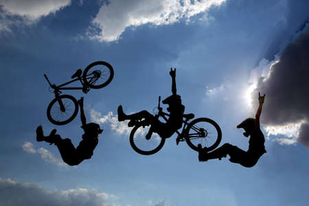 clouds making: An extreme rider is making a free style jump from a ramp. The young boy with his bicycle is seen as a silhouette in front of the sun. Multiple exposure image. Clouds. Stock Photo