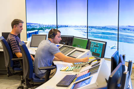 Sofia, Bulgaria - September 12, 2016: An air traffic controller is directing flights during a working day at Bullgaria's Air Traffic Services Authority control center room. Talking with the pilot.