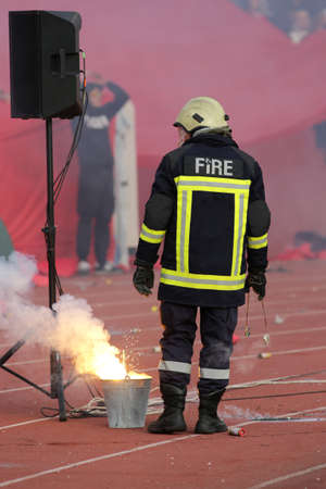 extinguishing: Firefighter putting down football fans torches fire during a match between Bulgarias CSKA and Levski