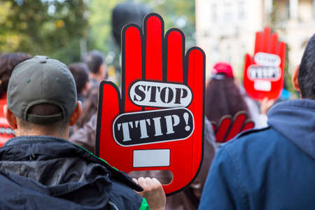 activists: Activists are holding red hand signs Stop TTIP during a demonstration against Free Trade Agreements TTIP, CETA and TISA between EU and U.S. in Sofia, Bulgaria. Editorial