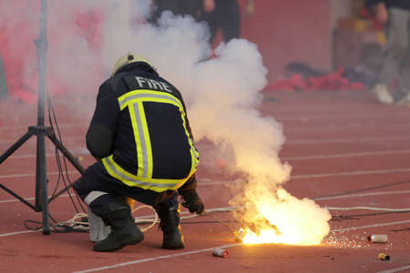Firefighter putting down football fans torches fire during a match between Bulgarias CSKA and Levski