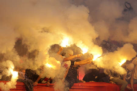 football fans: Sofia, Bulgaria - October 15, 2016: CSKAs football fans are holding torches in fire during a match between Bulgarias CSKA and Levski on the National stadium.