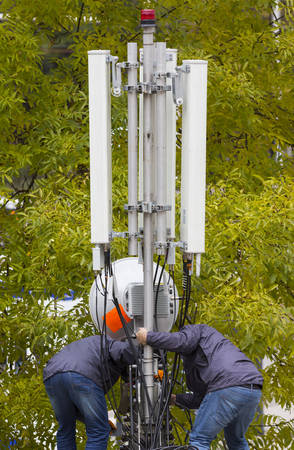 gsm: Workers repair a telecommunication (GSM) mobile antenna. GSM signal receiver close to the green trees.