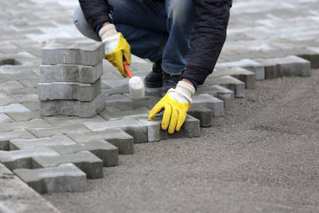 Paving stone worker is putting down pavers during a construction of a city street. Standard-Bild
