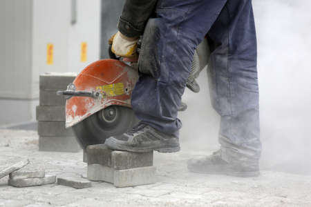 stabs: Worker uses a stone cutter to cut the brick pavers. Cutting concrete paving stabs using a cut-off saw. Paving stone saws working with power tools.