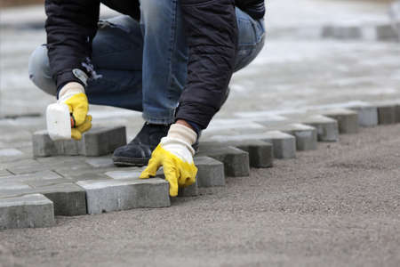 Paving stone worker is putting down pavers during a construction of a city street. Stock Photo
