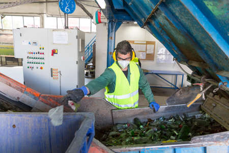 Sofia, Bulgaria - May 26, 2016: Glass waste worker is recycling glass bottles in a recycling facility. Different glass packaging bottle waste. Glass waste management. 新闻类图片