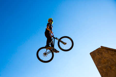 BACKFLIP: Sofia, Bulgaria - September 24, 2016: Silhouette of a biker jumping against the blue sky and the sun.