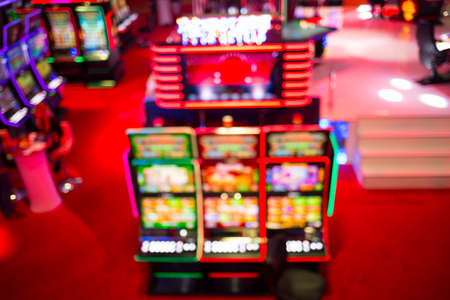 machines: Blurry image of slots machines and other gambling equipment at a casino. Out of focus (bokeh) colourful and high contrast picture in a casino.