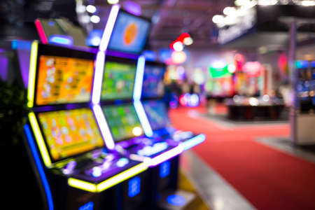 Blurry image of slots machines and other gambling equipment at a casino. Out of focus (bokeh) colourful and high contrast picture in a casino.
