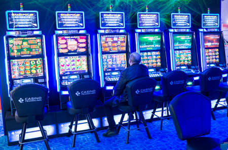 tragamonedas: Sofía, Bulgaria - 24 de noviembre 2016: Un hombre está jugando a las máquinas tragamonedas de juego en una exposición de máquinas de juegos de azar de casino y equipo en el Inter Expo Center en Sofía.