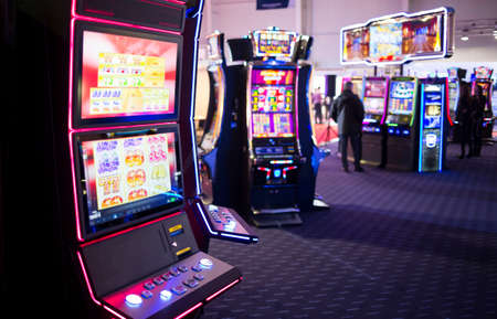 machines: A slot machine is seen in a casino room with people playing other slot machines in the background.
