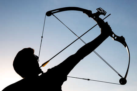 A silhouette of an archer draws his compound bow and aims upwards with clean blue sky as background. Stock Photo