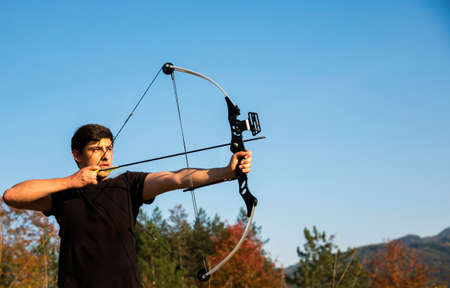 recurve: An archer draws his compound bow and aims upwards with clean blue sky as background. Stock Photo