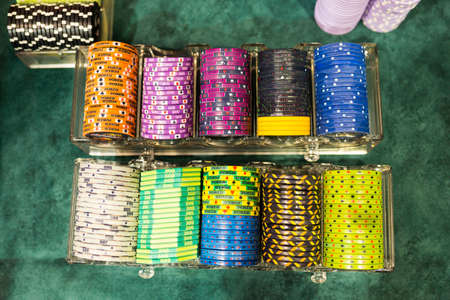 Colourful poker chips in a casino on a gambling table. Lots of chips with different nomination and colours.