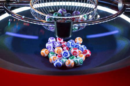 Colourful lottery balls in a rotating bingo machine.